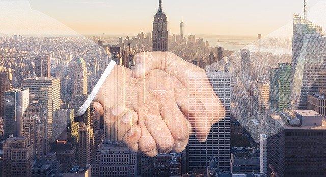 uścisk dłoni na tle panoramy miasta z drapaczami chmur
